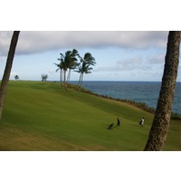 The fairway of Kauai Lagoons Golf Club's par-4 16th hole narrows and heads downhill towards the green.