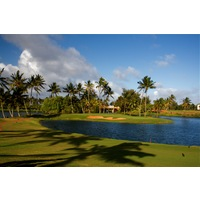 Kauai Lagoons Golf Club's 18th hole is a long par 4 that requires carry over water and into the trade winds.
