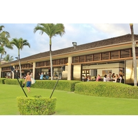 A surfer walks by as diners enjoy the great food and views at the Beach House Restaurant on Kauai.